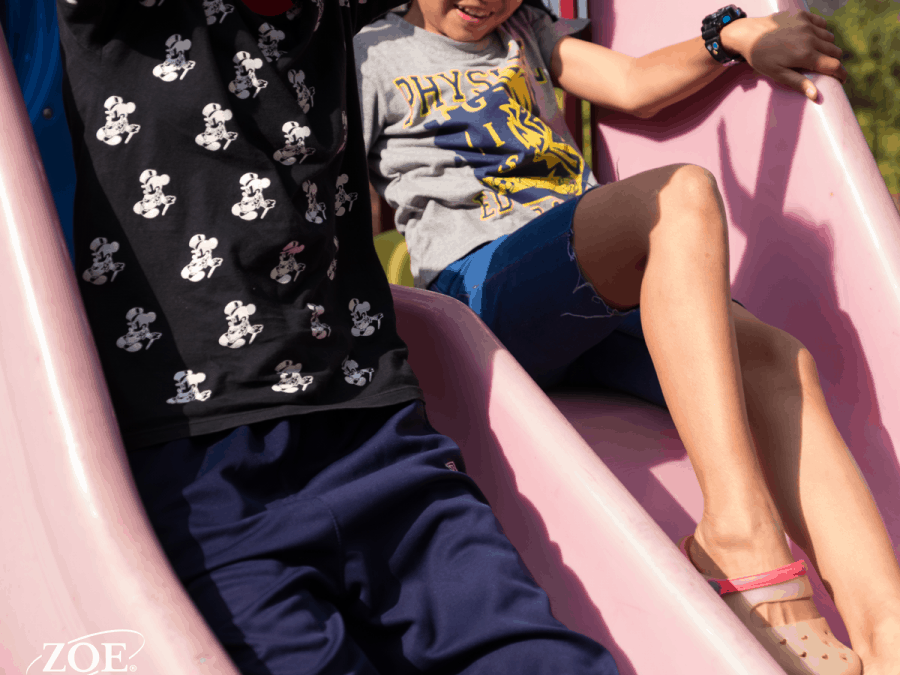 two children on a pink slide