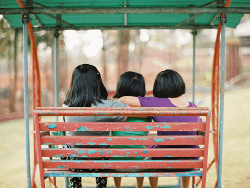 three girls sitting on a red bench with a green cover