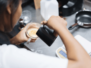 woman pouring frothed milk into a cup of coffee
