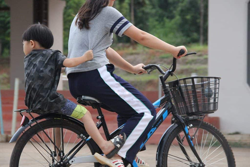 Asian child and mother riding on the bike