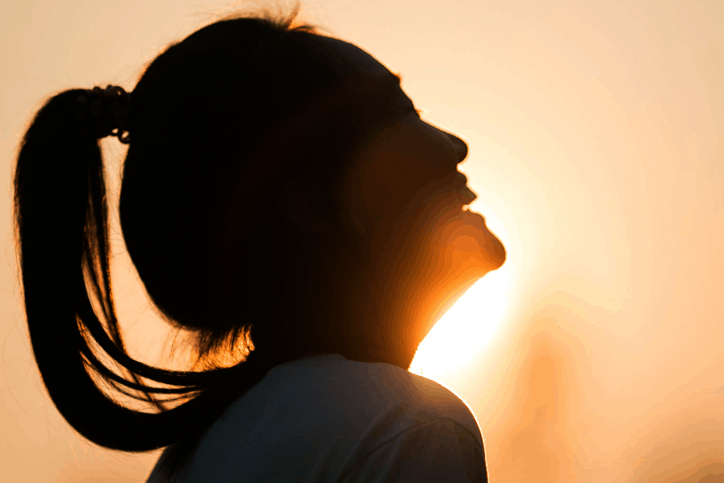 women silhouette smiling against the backdrop of the sun