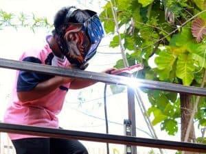 man welding a fence