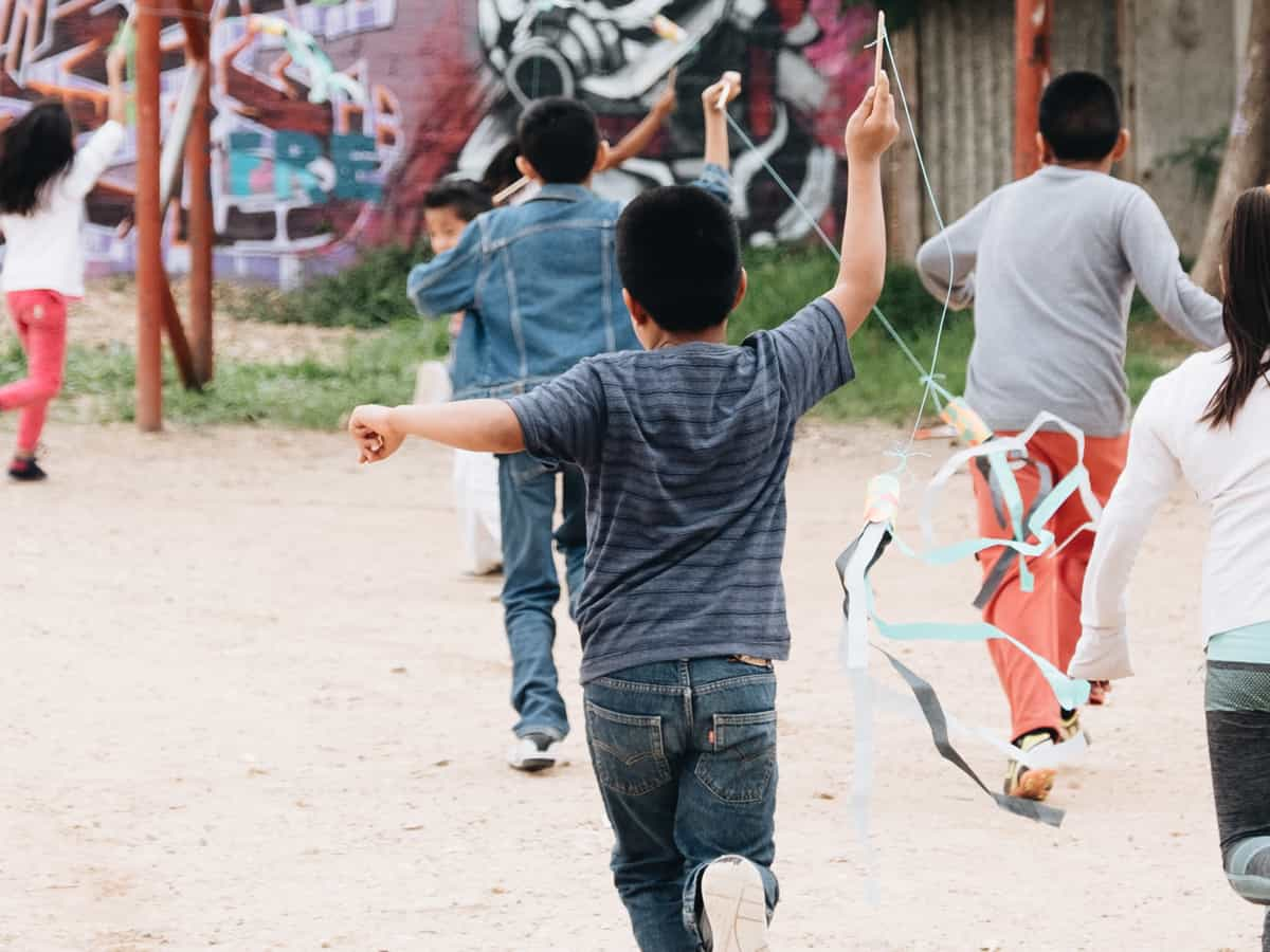 children in Mexico running with kites