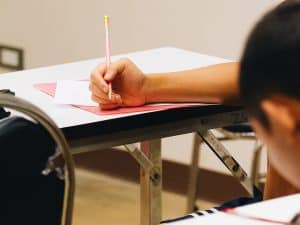 person with pencil in hand on a desk