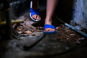 feet of child in sandals walking in dirty place